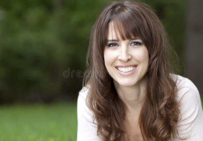 Portret kobieta ono uśmiecha się przy kamerą
