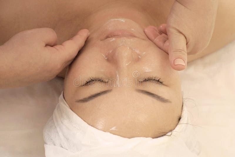 Portret kobieta otrzymywa Wellness masaż twarz Azjatycki pojawienie Kobieta z zamkniętymi oczami kłama na leżance przy fotografia royalty free