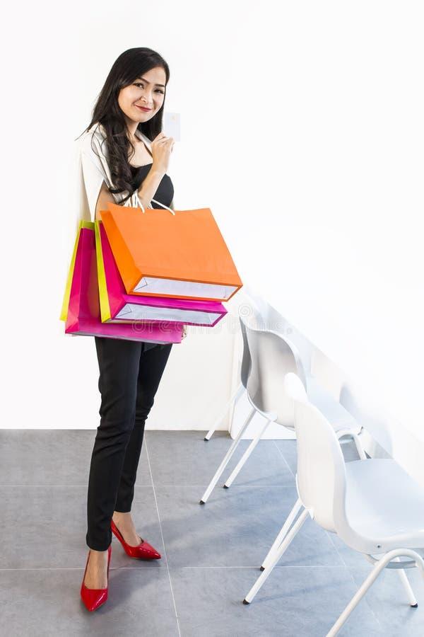 Portret kobieta w czarny i biały kostiumu mieniu barwił torba na zakupy i kredytową kartę Dziewczyna patrzeje uśmiechnięty i szcz zdjęcia stock