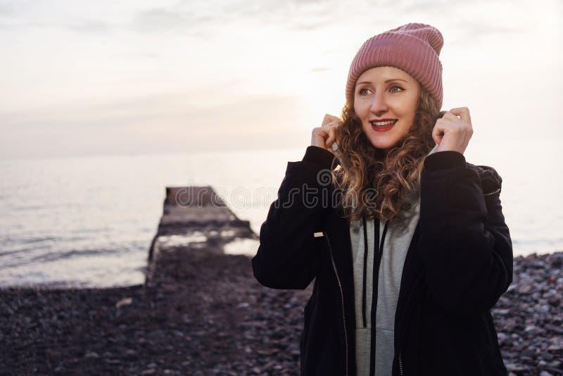 Portret kobieta w kurtki i kapeluszu pozycji na plaży przy zmierzchem Dziewczyna w sportswear chodzi w wieczór wzdłuż seashore obrazy royalty free