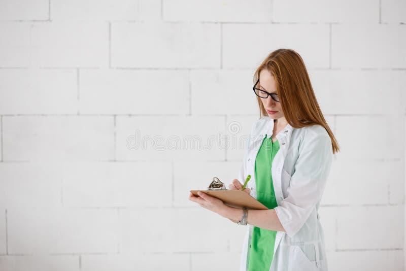 Portret kobiety lekarki ufnego medycznego fachowego writing cierpliwe notatki na białej szpitalnej klinice izolują tło obrazy royalty free
