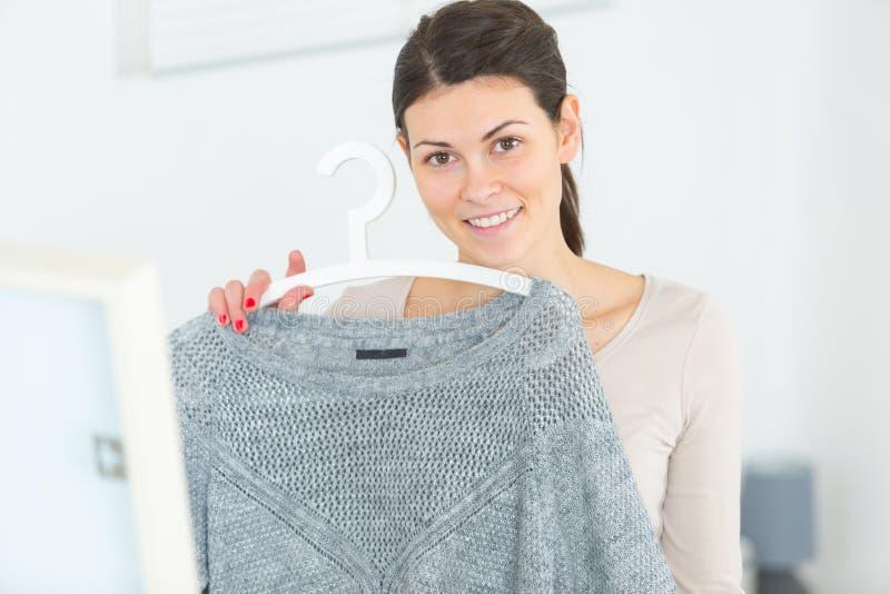 Portret kobiety mienia bluza na odzieżowym wieszaku fotografia stock