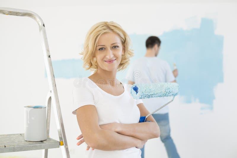 Portret kobiety mienia farby rolownik z mężczyzna obrazu ścianą w tle obrazy stock