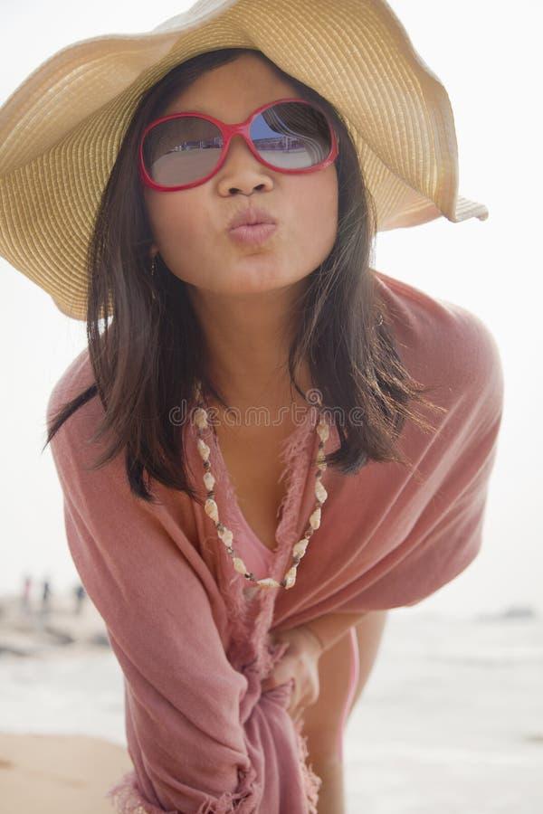 Portret kobiety na plażowej robi całowanie twarzy przy kamerą w opadającym słońce kapeluszu fotografia stock