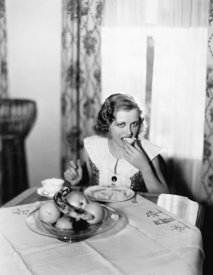 Portret kobiety obsiadanie przy łasowaniem kawałek chleb i stołem (Wszystkie persons przedstawiający no są długiego utrzymania i  obraz royalty free