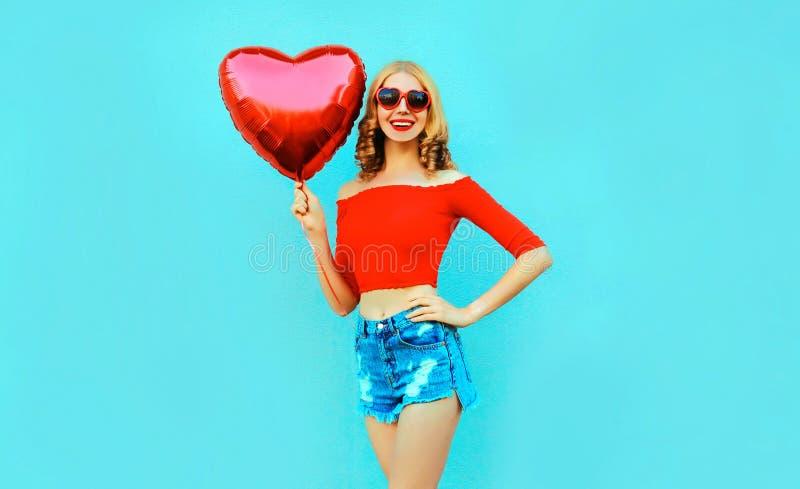 Portret kobiety szczęśliwego uśmiechniętego mienia czerwony serce kształtował lotniczego balon na kolorowym błękicie zdjęcie stock
