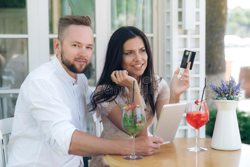 Portret kochający pary obsiadanie w kawiarni Mężczyzna i kobieta wydajemy czas wpólnie na pastylce, zegarek coś zdjęcia royalty free