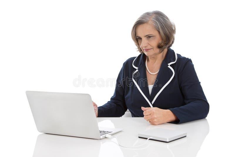 Portret: kompetentny starszy bizneswomanu obsiadanie przy biurkiem z co obraz royalty free