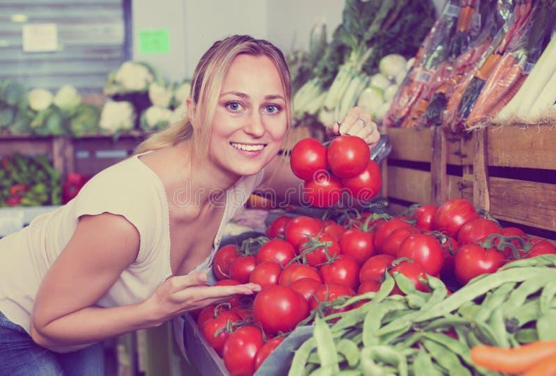 Portret kupuje organicznie pomidory w sklepie kobieta obraz royalty free
