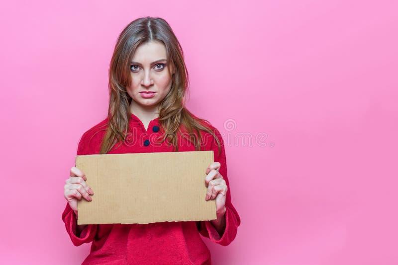 Portret kwaad mooi jong donkerbruin meisje met lang haire in rode pyjama's met een kartonteken in handen malplaatje stock foto