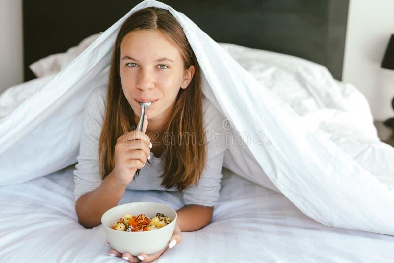 Portret 12-13-14 lat nastoletnia dziewczyna je zdrowego posiłek w łóżku fotografia royalty free