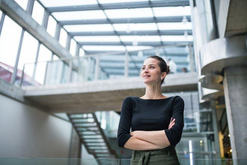 Portret młoda bizneswoman pozycja w korytarzu na zewnątrz biura, ręki krzyżować zdjęcie royalty free
