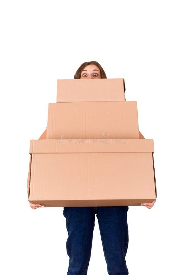 Portret młoda doręczeniowa kobieta patrzeje za pudełkami i trzyma pakuneczek odizolowywający na białym tle zdjęcia royalty free