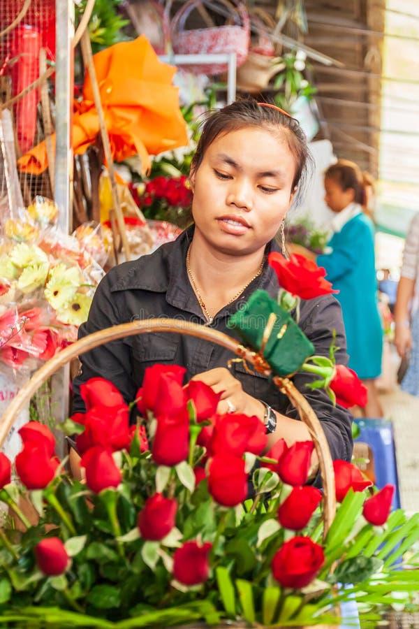 Portret młode khmer kwiaciarni kobiety robi piękno bukietowi czerwone róże na footpath Phsa Thmei rynek, Phnom Penh, Kambodża fotografia stock