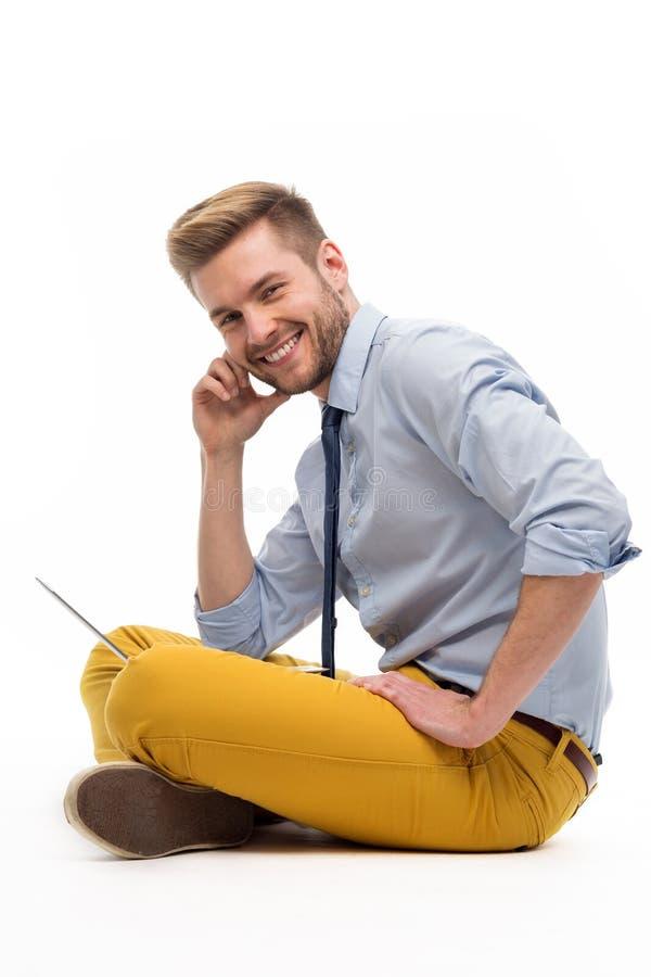 Portret młodego człowieka obsiadanie na podłodze z laptopem fotografia stock