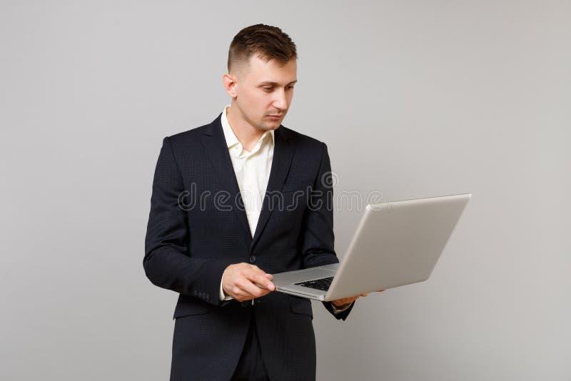 Portret młody biznesowy mężczyzna w klasycznym czarnym kostiumu i koszula pracuje na laptopu komputeru osobistego komputerze odiz obrazy royalty free