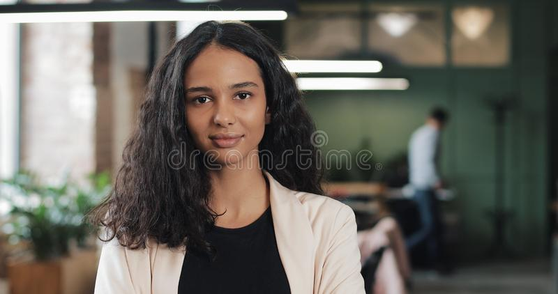 Portret młody pomyślny bizneswoman przy ruchliwie biurem Przystojny żeński pracownik patrzeje kamerę i robi kciukom obrazy stock