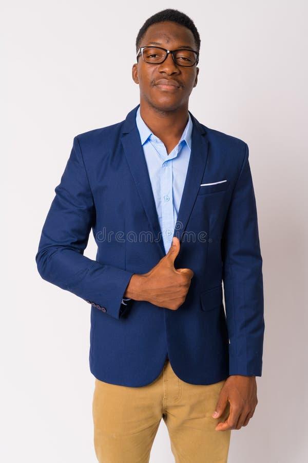 Portret młody przystojny Afrykański biznesmen w kostiumu daje aprobatom obrazy stock