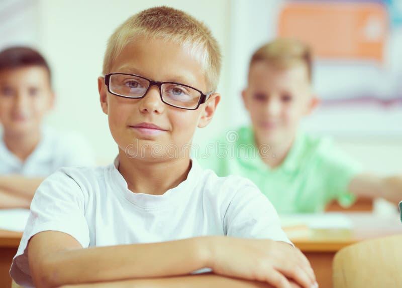 Portret mądry ucznia obsiadanie przy learnin i stołem obraz stock