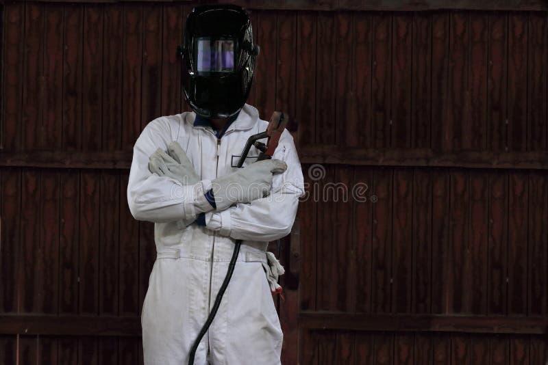 Portret mądrze spawacza mężczyzna z pochodnią i ochronny hełm w bielu mundurujemy w fabryce koncepcja przemysłowe fotografia stock