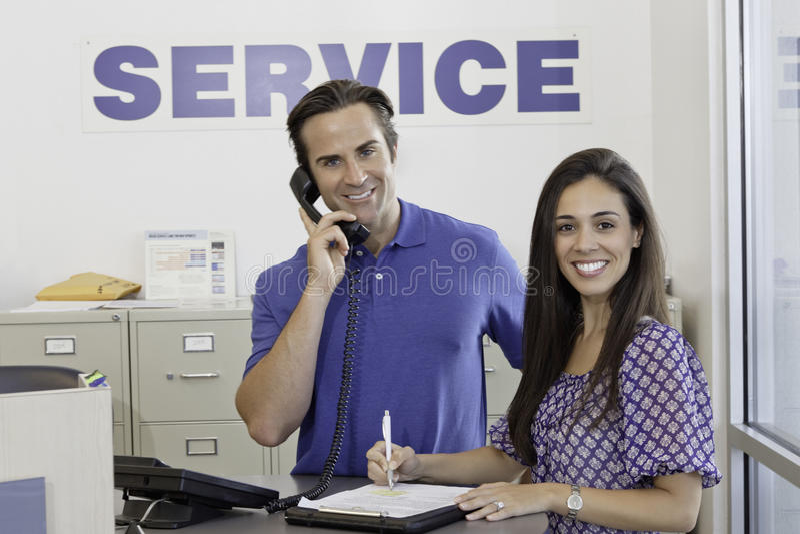 Portret mężczyzna i kobiety pozycja w auto remontowym sklepie fotografia royalty free