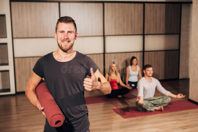 Portret mężczyzna mienia joga matowy i seans aprobaty fotografia stock