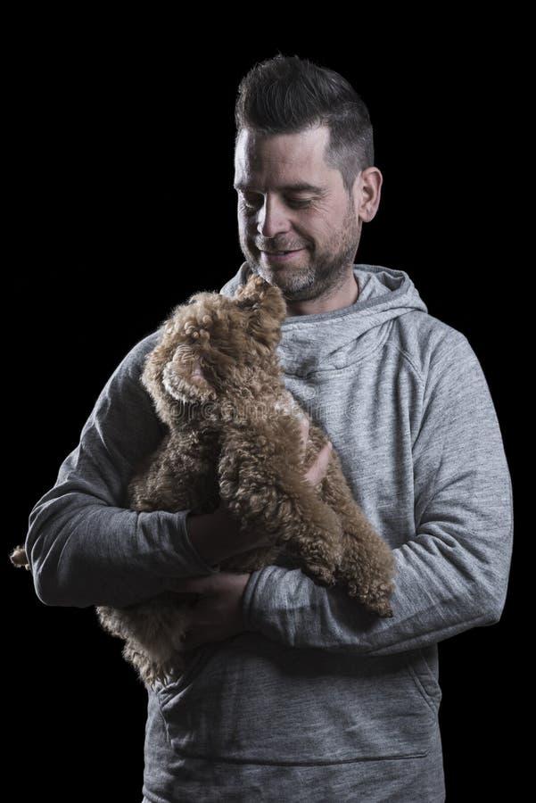 Portret mężczyzna patrzeje małego czerwonego zabawkarskiego pudla psa Czarny t?o pionowo obrazy stock