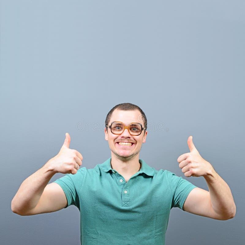 Portret mężczyzna pokazuje kciuk w górę znaka z pustą przestrzenią nad jego głowa dla twój teksta przeciw szaremu tłu obrazy stock