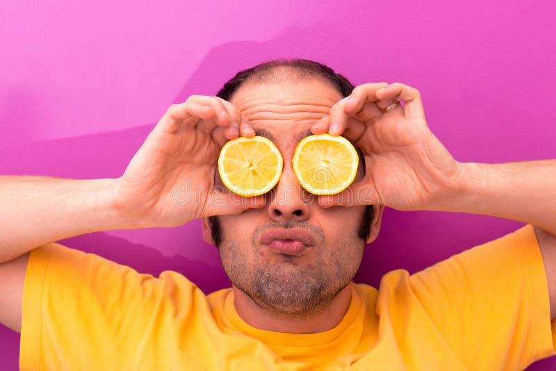 Portret mężczyzna trzyma dwa pokrajać cytryny w jego oczach fotografia royalty free
