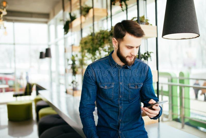 Portret mężczyzna use telefon komórkowy w kawiarni zdjęcia stock