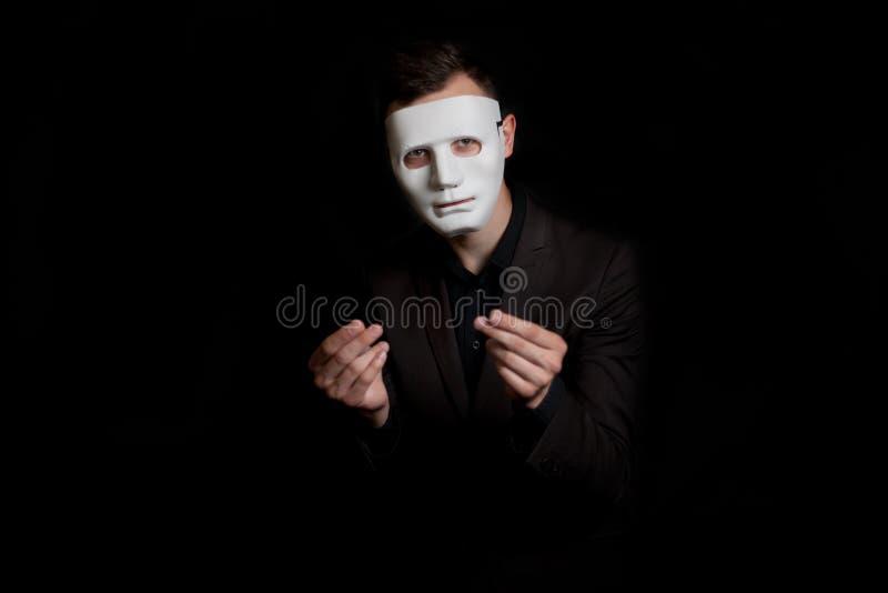 Portret mężczyzna w białej masce na czarnym tle Pokazuje gest pieniądze Wymaga pieniądze fotografia royalty free