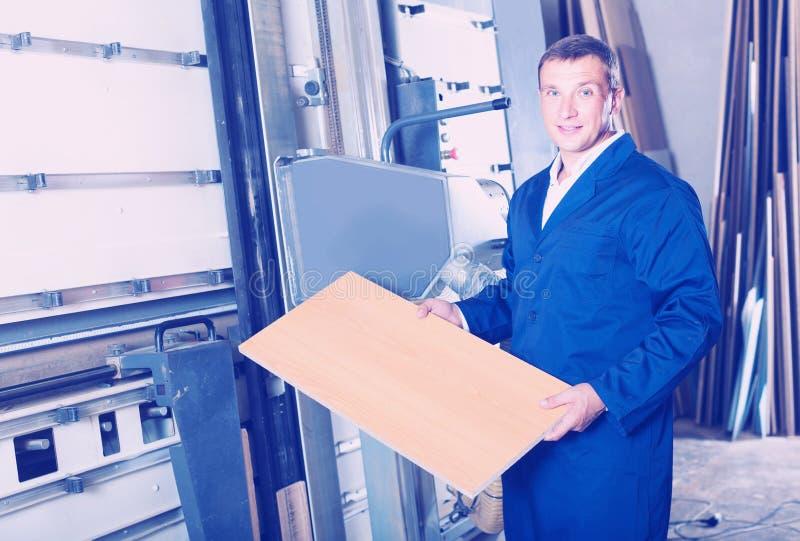 Portret mężczyzna w jednolitym działaniu na wielkim automatycznym saw machina obraz stock
