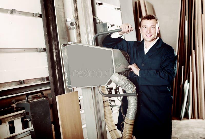 Portret mężczyzna w jednolitym działaniu na wielkim automatycznym saw machina obrazy royalty free