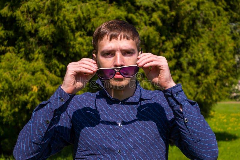 Portret m??czyzna w okularach przeciws?onecznych i b??kitny koszulowy trwanie outside w parku zdjęcie stock