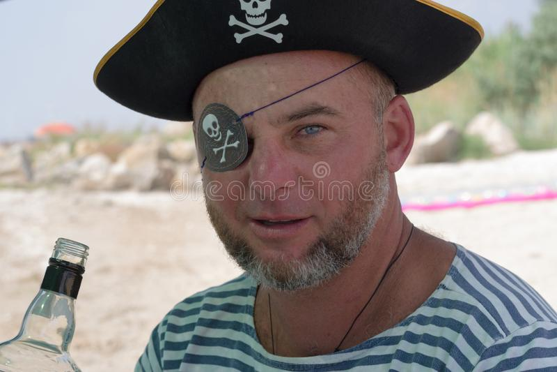 Portret mężczyzna w pirata kostiumu na plaży z butelką zdjęcie stock