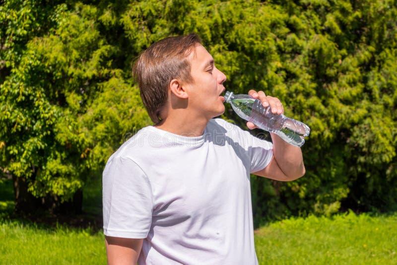 Portret mężczyzna woda pitna od butelki w biały koszulki stać outside w parku, fotografia royalty free