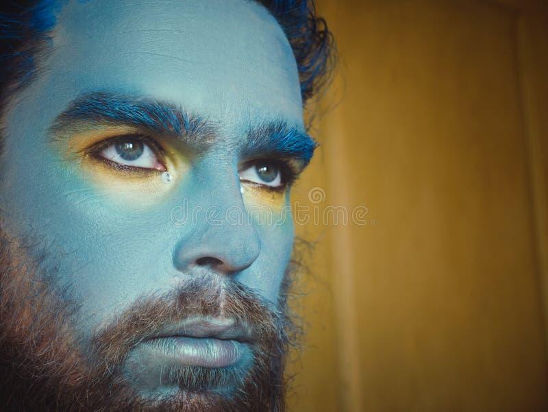 Portret mężczyzna z błękitnym makijażem na jego twarzy Reżyseruje makijaż, jak obcy, fantazja obrazy royalty free