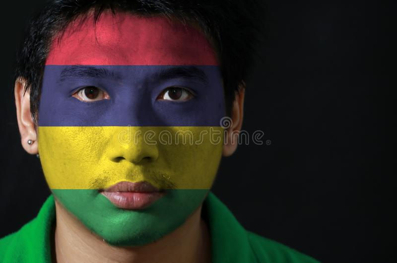 Portret mężczyzna z flagą Mauritius malował na jego twarzy na czarnym tle obraz royalty free