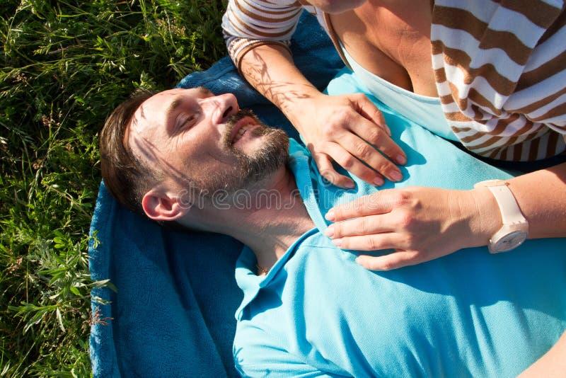 Portret mężczyzna z kobiet rękami na jego klatka piersiowa Uśmiechniętym mężczyzna kłaść na błękitnej koc i zielonej trawie z ręk obrazy stock