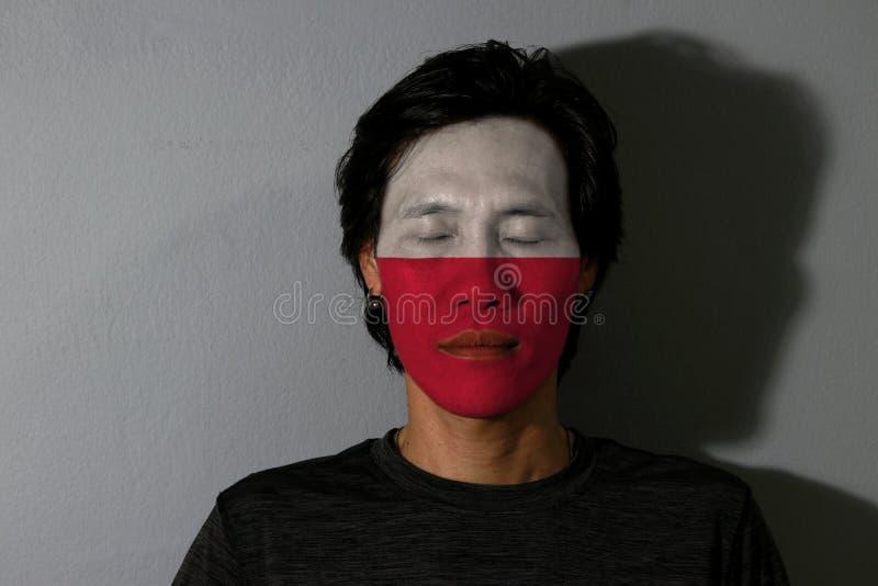 Portret mężczyzna z Polska flagą malującą na jego twarzy i zamyka oczy z czarnym cieniem na popielatym tle zdjęcia royalty free