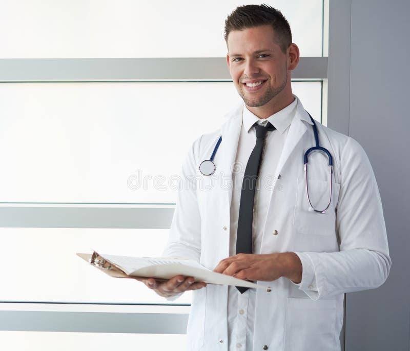 Portret męska lekarka trzyma jego cierpliwą mapę w jaskrawym nowożytnym szpitalu zdjęcia stock