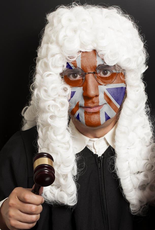 Portret męski angielski prawnik z malującym Brytyjski Union Jack flaga mienia sędziego młoteczkiem zdjęcie stock
