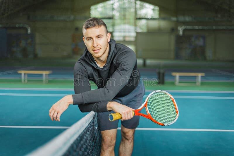 Portret męski gracz w tenisa młody facet blisko sieci na dworskim mieniu kant w jego wręcza obrazy royalty free