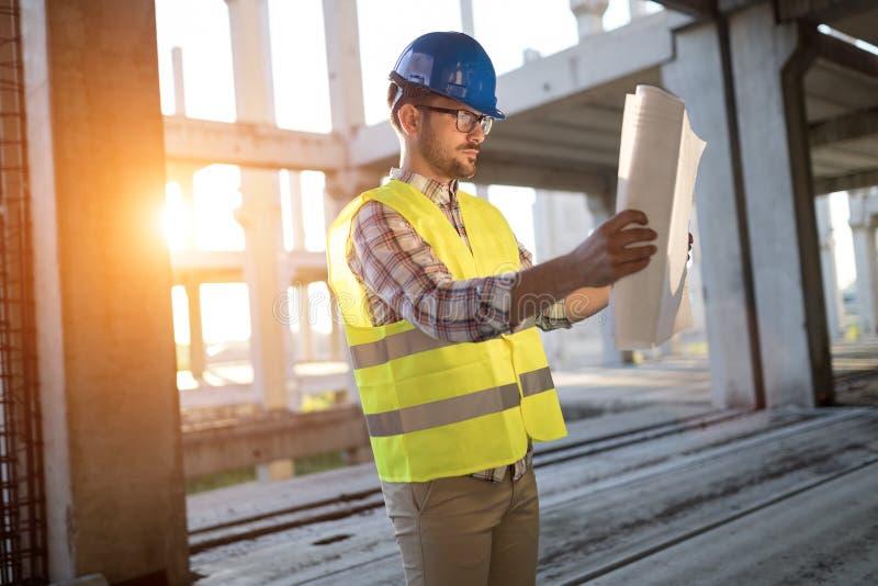 Portret męski miejsce kontrahenta inżynier trzyma błękitnego druku papier z ciężkim kapeluszem zdjęcie stock