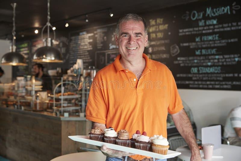 Portret Męski właściciel Z tacą Muffins W sklep z kawą obraz royalty free