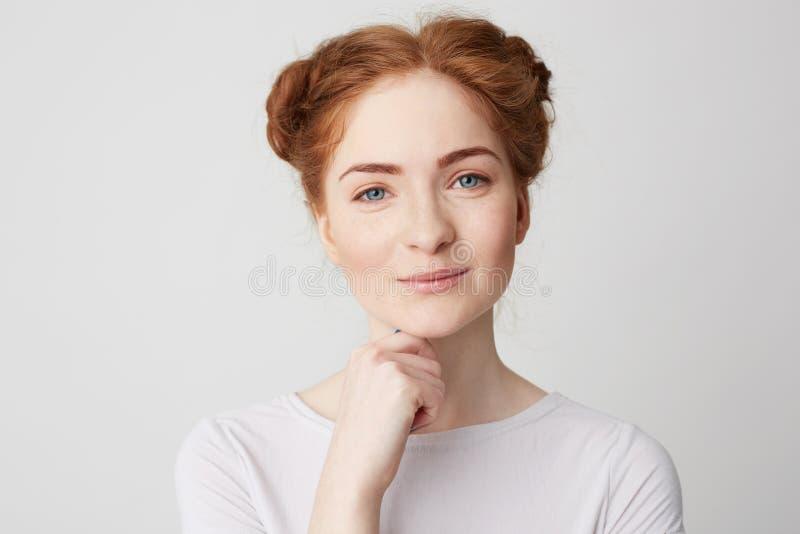 Portret młoda ładna dziewczyna z czerwonym włosianym ono uśmiecha się patrzeje kamera wzruszającym podbródkiem nad białym tłem zdjęcia royalty free