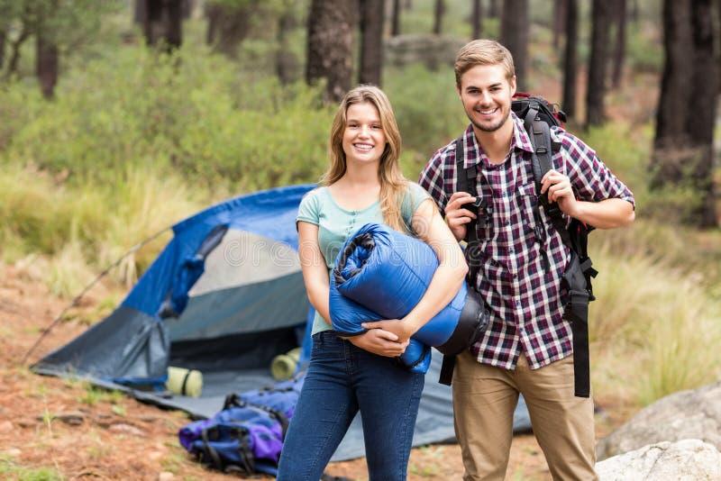 Portret młoda ładna wycieczkowicz para trzyma sypialną torbę plecaka i zdjęcie stock