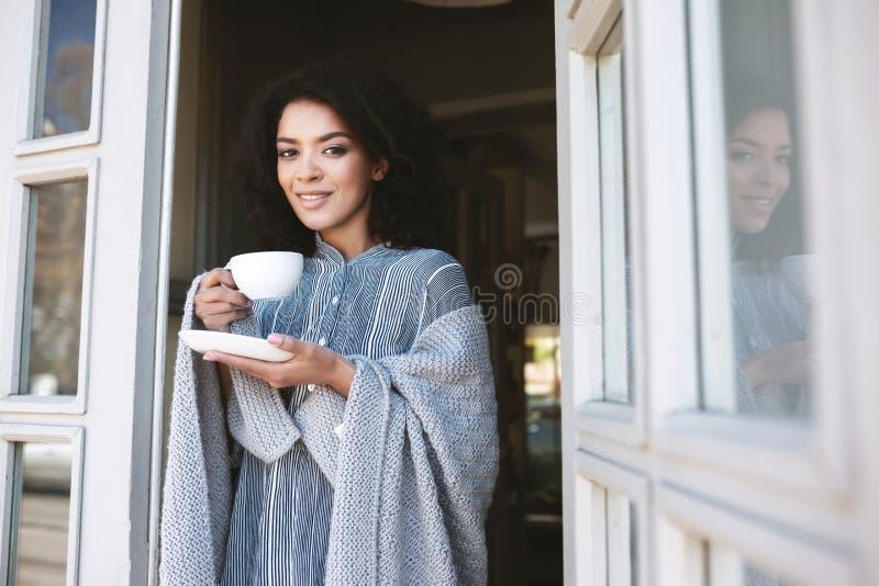 Portret młoda amerykanin afrykańskiego pochodzenia dziewczyna zawijająca w szkockiej kracie pije kawę w restauracyjnej Ładnej uśm zdjęcie royalty free