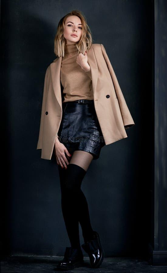 Portret młoda atrakcyjna ładna blondynki kobieta w beżowej kurtki i skóry koszula, getry, patentów buty zdjęcia royalty free
