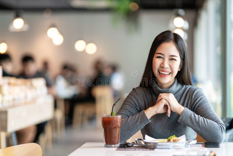 Portret młoda atrakcyjna azjatykcia kobieta patrzeje kamerę ono uśmiecha się z pozytywnym miastowym stylu życia pojęciem fotografia royalty free
